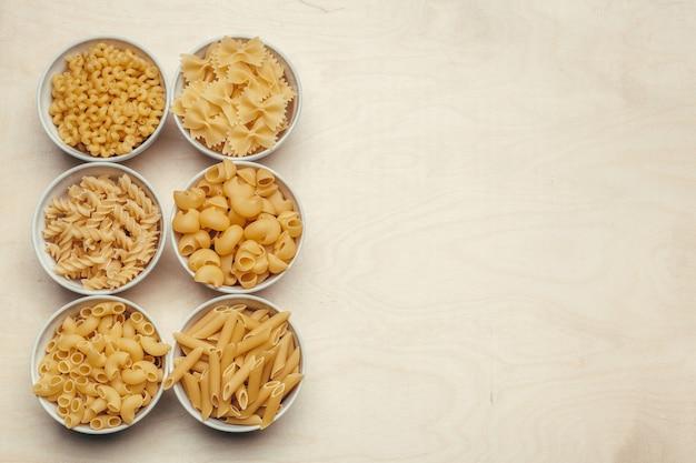 Diversi tipi di pasta in ciotole sul tavolo.