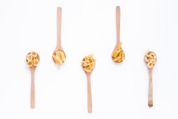 Diversi tipi di pasta italiana cruda sul cucchiaio di legno su superficie bianca