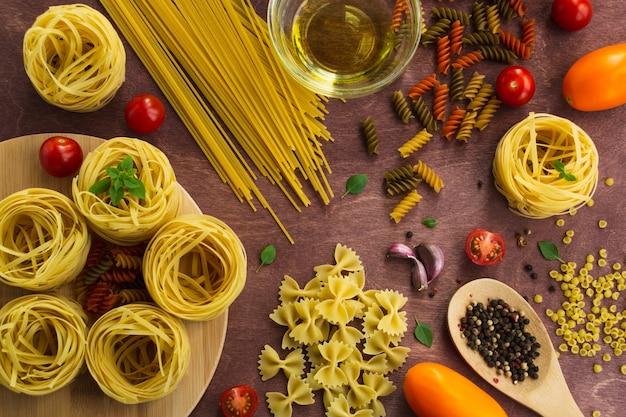 Diversi tipi di pasta su un tavolo di legno.