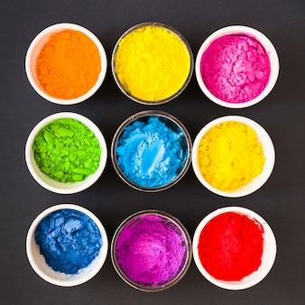 Diversi tipi di polvere colorata di holi nella ciotola bianca e vetro su sfondo nero