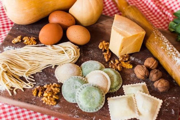 Diversi tipi di ravioli crudi con ingredienti sul tagliere di legno