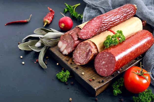 Diversi tipi di salsiccia, verdure fresche e verdure su uno sfondo nero.