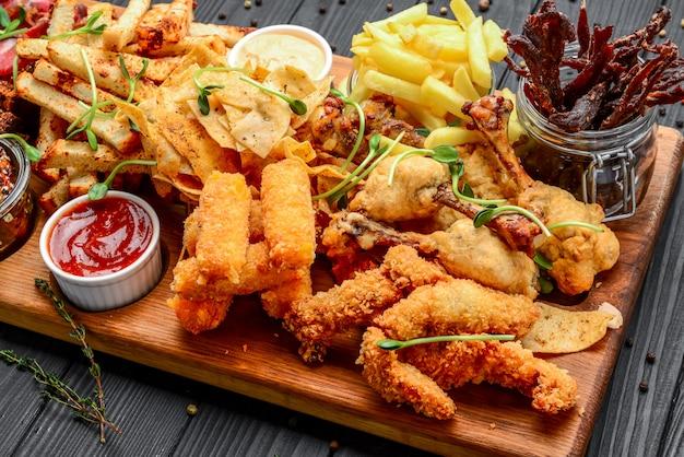 Diversi tipi di snack fritti: pollo, formaggio, anelli di cipolla e calamari, gamberetti e funghi