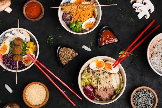 Diversi tipi di spaghetti ramen in stile asiatico con salsa; semi di sesamo e di riso su sfondo nero con texture