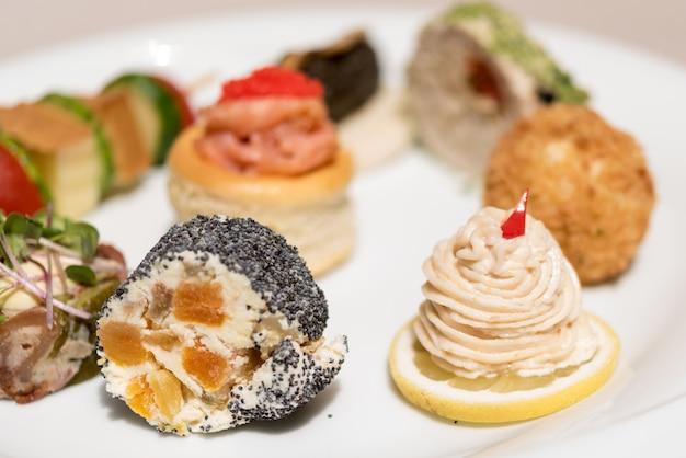 Diversi tipi di tartine, disposti su piatti bianchi, finger food