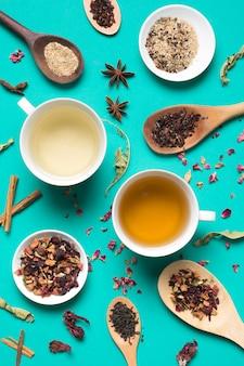 Diversi tipi di tazze da tè bianco con spezie ed erbe sullo sfondo turchese