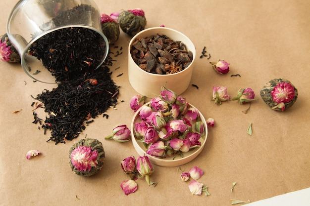 Diversi tipi di tè si sono rovesciati sullo sfondo marrone