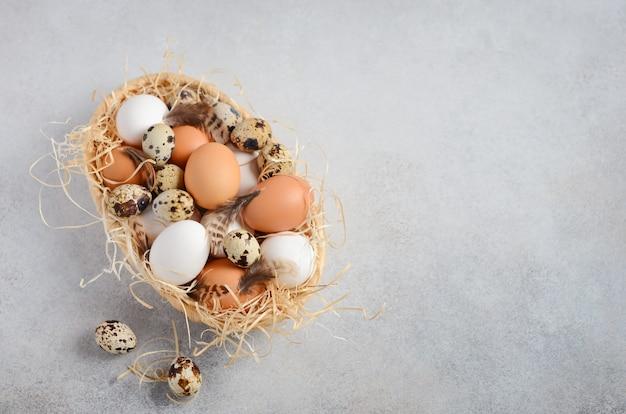 Diversi tipi di uova in un cesto su uno sfondo grigio cemento.