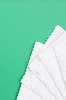 Diversi tovaglioli di carta bianca si trovano su uno sfondo di plastica verde