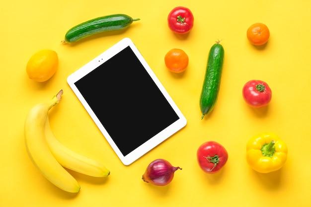 Diverso alimento salutare - peperone, pomodori, banane, cetriolo verde, cipolle, limone, tavoletta con schermo nero