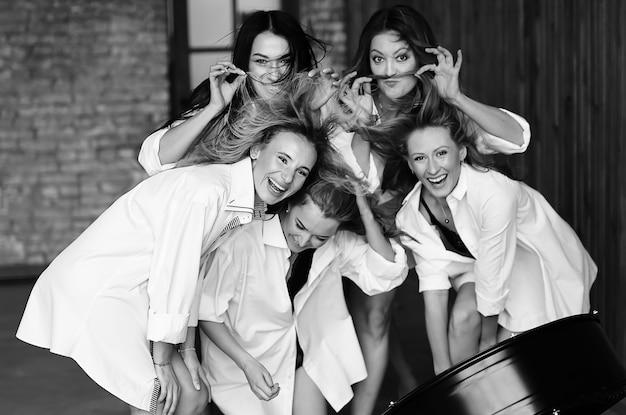 Diverso gruppo di amici femminili godendo ad una festa e ridendo. gruppo di belle donne felici divertendosi in vestiti bianchi.