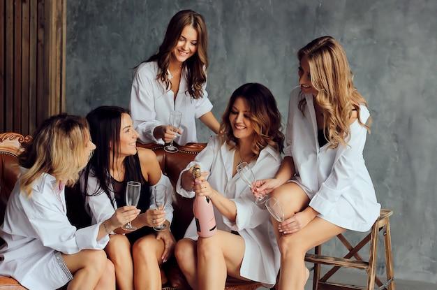 Diverso gruppo di amici femminili godendo ad una festa e ridendo.