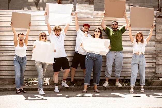 Diverso gruppo di persone che protestano con segni vuoti. protesta contro i diritti umani, abuso di libertà, questioni sociali
