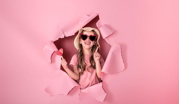 Divertente bambina guarda fuori dal buco in un cappello da spiaggia e occhiali a forma di cuore, che tiene un cuore su un bastone, su uno sfondo colorato, un posto per il testo, riprese in studio