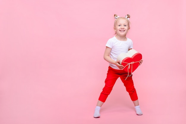 Divertente bambina in una maglietta bianca e pantaloni rossi con una scatola a forma di cuore su uno sfondo rosa. ritratto per bambini con spazio per il testo.
