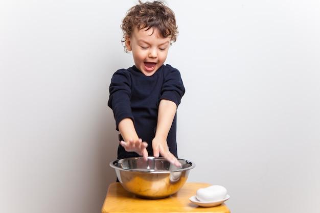 Divertente bambino carino lava le mani con sapone.