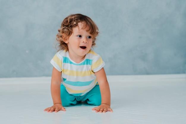 Divertente carino riccio bambino si siede a giocare in macchina su un pavimento bianco sullo sfondo del muro grigio.