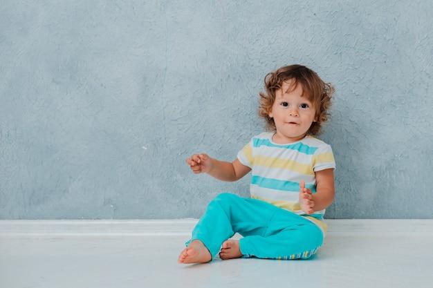 Divertente carino riccio bambino si siede giocando in macchina su un pavimento bianco sullo sfondo del muro grigio.