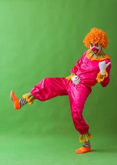 Divertente clown giocoso in parrucca arancione imitando a suonare la chitarra.