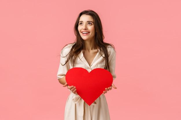 Divertente e spensierata bella donna europea in abito, con in mano una carta di san valentino, un grande cuore rosso, guardando a sinistra stupita e felice, sorridente impressionata, in piedi rosa muro gioioso