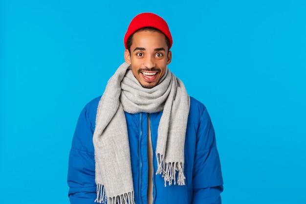 Divertente ed eccitato sorridente bel giovane ragazzo afro-americano hipster in berretto rosso alla moda, sciarpa e giacca imbottita invernale, sorridendo stupito e curioso, in piedi parete blu