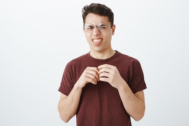 Divertente giovane distrutto in occhiali rotondi e maglietta rossa