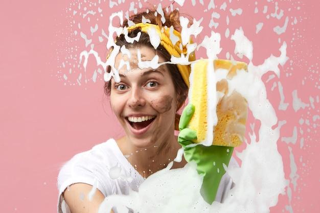 Divertente governante allegra con macchie sporche sul viso che fa le pulizie di primavera a casa, spazzando via la schiuma densa e spessa dal vetro della finestra o dallo specchio usando uno straccio, un detergente e guanti di gomma protettivi