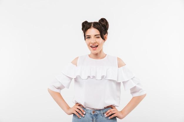 Divertente ragazza che indossa l'acconciatura doppi panini e parentesi graffe dentali ammiccanti e sorridenti a voi, isolato su bianco