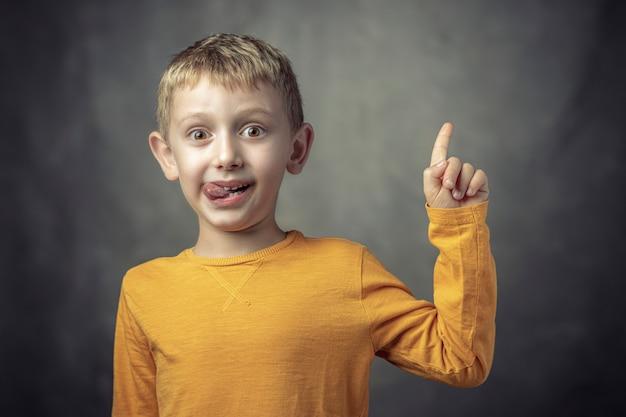 Divertente ritratto di un bambino caucasico di 6 anni con la lingua sporgente.