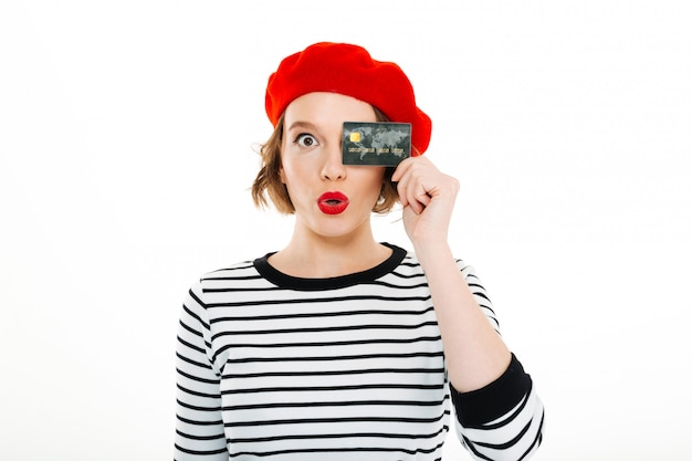 Divertente signora stupita copre l'occhio con carta di credito e guardando la fotocamera