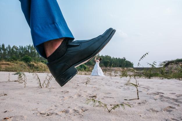 Divertente sposa asiatica e sposo caucasico posting scherzo con i piedi in alto