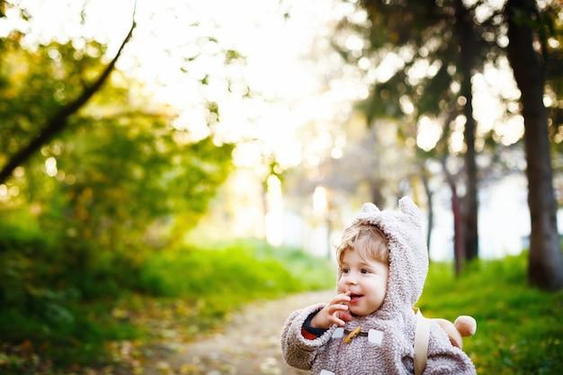 Divertente timido piccolo bambino di 2 anni ridacchiando nel parco al tramonto. concetto di infanzia felice. spazio per il tuo testo.