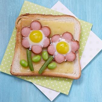 Divertente toast con formaggio e fiori di salsicce, fagiolini e uova di quaglia