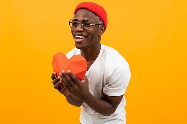 Divertente uomo africano con un bel sorriso in una maglietta bianca tiene fuori un modello 3d rosso di un cuore fatto di carta per san valentino su uno sfondo giallo