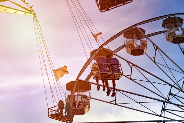 Divertimento nel lunapark, gente sulle montagne russe e la grande ruota, il tramonto