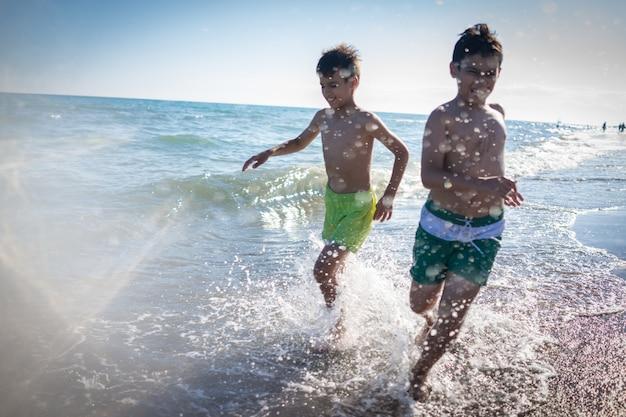 Divertimento per bambini che giocano splash in spiaggia
