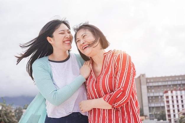 Divertiresi asiatico della figlia e della madre all'aperto - gente di famiglia felice che gode insieme del tempo intorno alla città in asia