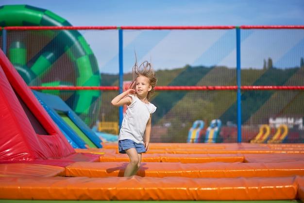Divertiresi grazioso della bambina all'aperto. saltando sul trampolino nella zona dei bambini. ragazza felice che salta sul trampolino giallo nel parco divertimenti