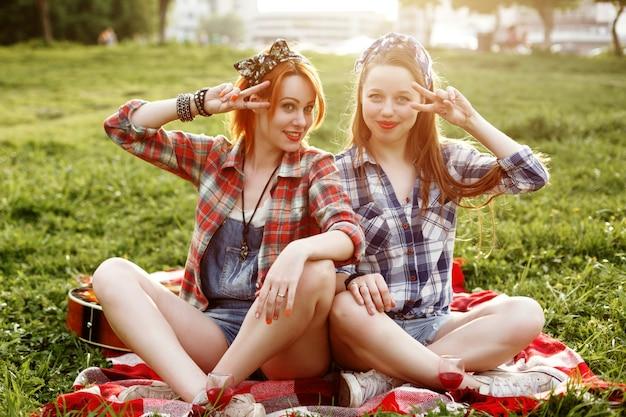 Divertiresi sorridente di due giovani ragazze dei pantaloni a vita bassa