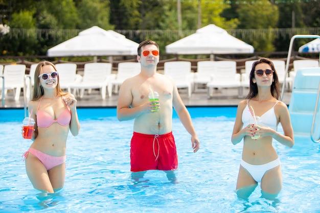 Divertirsi e gustare cocktail con i migliori amici. belle ragazze e ragazzo che trascorrono le loro vacanze estive e le vacanze.