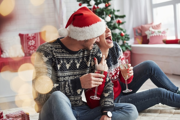 Divertirsi e ridere. due persone siedono sul pavimento e festeggiano il nuovo anno