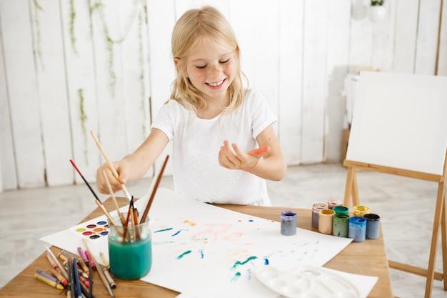 Divertirsi, gioioso, sorridente con i denti ragazza bionda di sette anni che gocciola vernice su un foglio di carta bianca distesa su un tavolo. bambino creativo divertirsi, godersi la pittura.