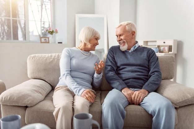 Divertirsi insieme. allegra coppia di anziani seduti sul divano in soggiorno e ridendo mentre scherza insieme
