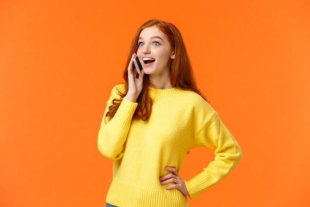 Divertito e sorpreso sorridente ragazza rossa allarga gli occhi e sembra impressionato mentre ascolta una buona notizia da un amico mentre parla al telefono, tenendo lo smartphone vicino all'orecchio, parla
