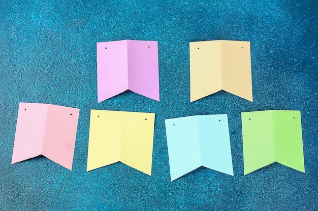 Diy pasqua ghirlanda, bandiere pasqua fatta di carta di sfondo blu.