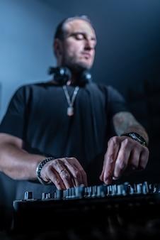 Dj che suona musica house e techno in un night club. mescolando e controllando la musica.