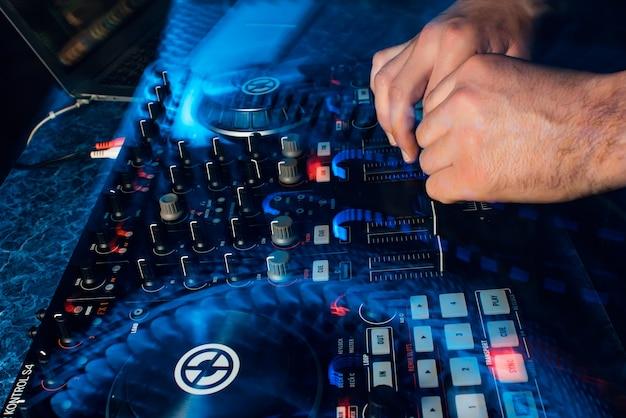 Dj che suona musica sul mixer contemporaneo professionale spostando i controller