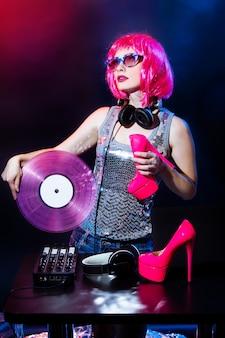 Dj con cuffie, capelli rosa e dischi in vinile rosa