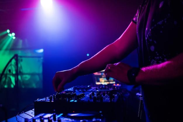 Dj in night club suonando in un mixer professionale, faretti che cambiano colore