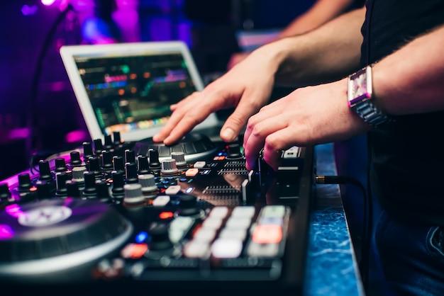 Dj in uno stand suonando un mixer in un night club